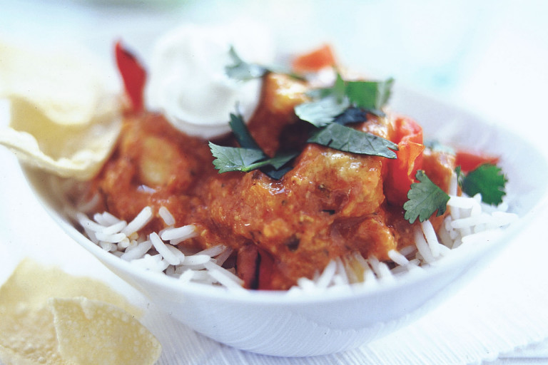 Quorn Pieces tikka masala on a bed of rice topped with yoghurt and coriander.
