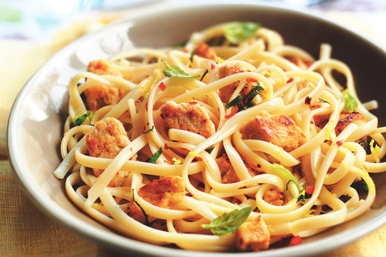 A taupe bowl of linguine topped with Quorn Pieces, chili flakes, and basil on an ochre tablecloth.