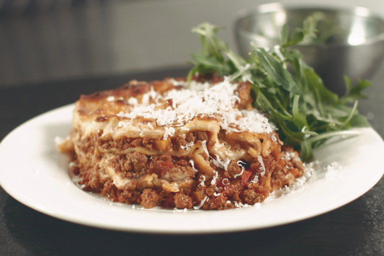 A portion of vegetarian lasagne made with Quorn Mince topped with Parmesan cheese served with a side of rocket in a white bowl