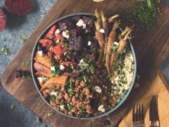 A bowl of bulgur wheat topped with Quorn Grounds, roasted carrots, roasted beets, sweet potato, and bell pepper topped with green onions, dried cranberries, and pumpkin seeds.