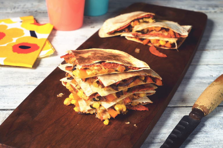 Vegan quesadilla made with Quorn Vegan Pepperoni slices in tortilla wraps, stacked on top of each other on a wooden board
