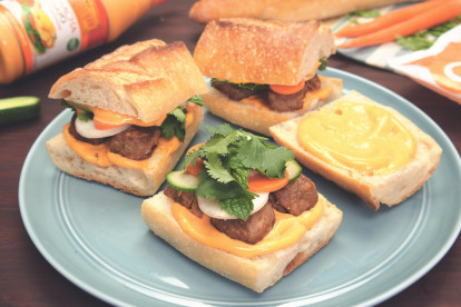 Two small banh mi sandwiches with pickled carrots and daikon, cucumber, Quorn Meatballs, cilantro, mint, and sriracha mayo on a baguette atop a blue plate.