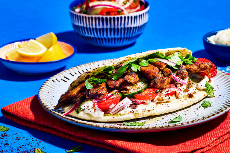 A pitta topped with Quorn Makes Amazing Turkish Style Kebab, tomatoes, cucumber, red onion, yoghurt sauce, and herbs on a red placemat on a cobalt blue background.