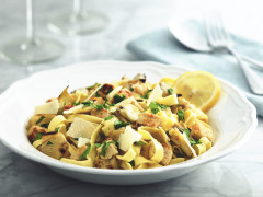 A white bowl full of tagliatelle pasta topped with Quorn Pieces, artichokes, parsley and parmesan, garnished with a lemon slice against a background of two wine glasses and a fork and spoon on a light blue napkin.