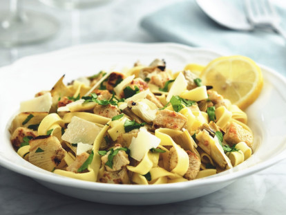 Tagliatelle pasta with Quorn Pieces and artichokes topped with cheese and parsley with a lemon wedge on the side.
