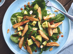 A spinach salad topped with diced avocado, sliced Quorn Fillets, dressing, and toasted almonds.