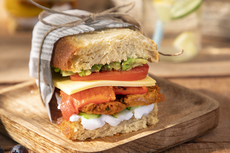 Wooden board with two Quorn sandwiches on next to Quorn Makes Amazing Peri-Peri Strips
