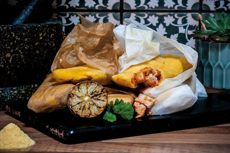 Mexican-style tamales made with Quorn Pieces wrapped in paper piled next to a molcajete with charred citrus and fresh coriander on the side.