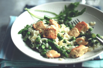 Risotto with peas, asparagus, and Quorn Pieces garnished with basil in a white bowl.