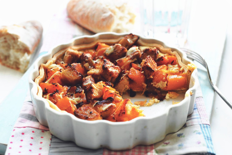 A tart filled with Quorn Pieces, butternut squash, and goat cheese in a white dish with a baguette in the background.