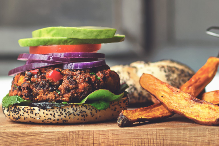A veggie burger on a poppyseed bun topped with lettuce, tomato, red onions, and avocado with thick-cut fries on the side.
