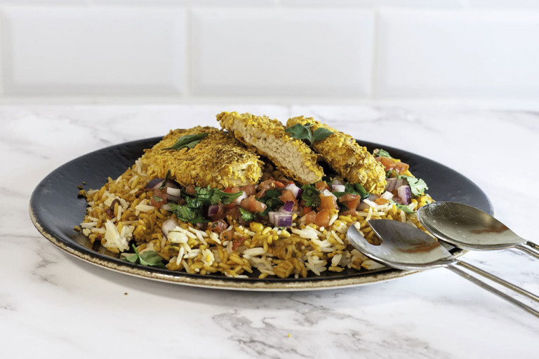 Dorito-crumbed Quorn Fillets atop a bed of rice with a tomato, red onion, and coriander salsa.
