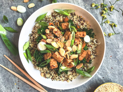 A bowl of quinoa topped with Quorn Pieces, kale, green onions, sesame seeds and peanuts.