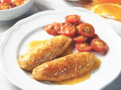 Quorn Fillets in an orange glaze with a side of cherry tomatoes on a white plate with an orange slice in the background.