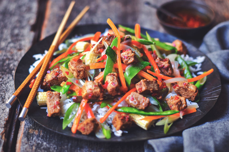 Quorn Pieces stir-fried with pepper, carrots, snow peas, and broccolini atop rice on a black plate with a pair of chopsticks.