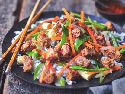 Healthy stir fry made with Quorn Vegan Pieces, mangetout and shredded carrot, served on a bed of rice on a plate with chopsticks