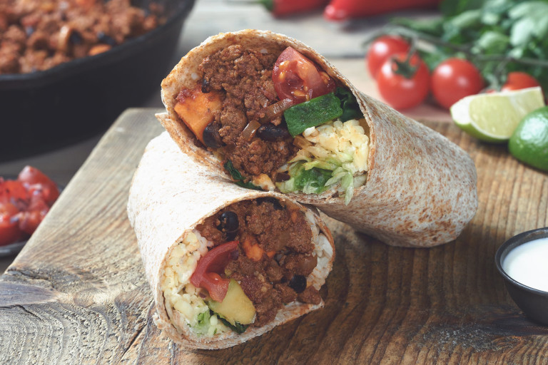 Vegetarian burrito sliced in half and stuffed with Quorn Mince, sweet potato, tomato and cheese served on a wooden board