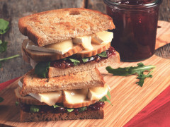 Two wholegrain bread sandwiches filled with Quorn Roast, cranberry sauce, brie, and rocket.