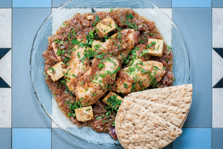 A glass bowl of doro wat made with Quorn Fillets on a blue tile background with two pieces of flatbread on the side.