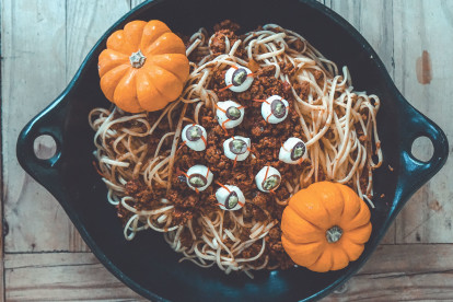 A bowl of spaghetti with Quorn Grounds Bolognese sauce topped with mozzarella 'eyes' and two mini pumpkins as décor.