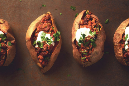 Four sweet potatoes split and stuffed with chili and topped with sour cream and parsley.