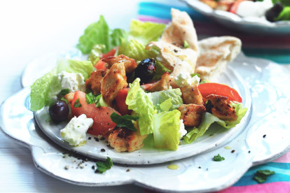 Romaine lettuce, feta cheese, sliced tomatoes, olives, and Quorn Pieces on a white plate with flatbread on the side.