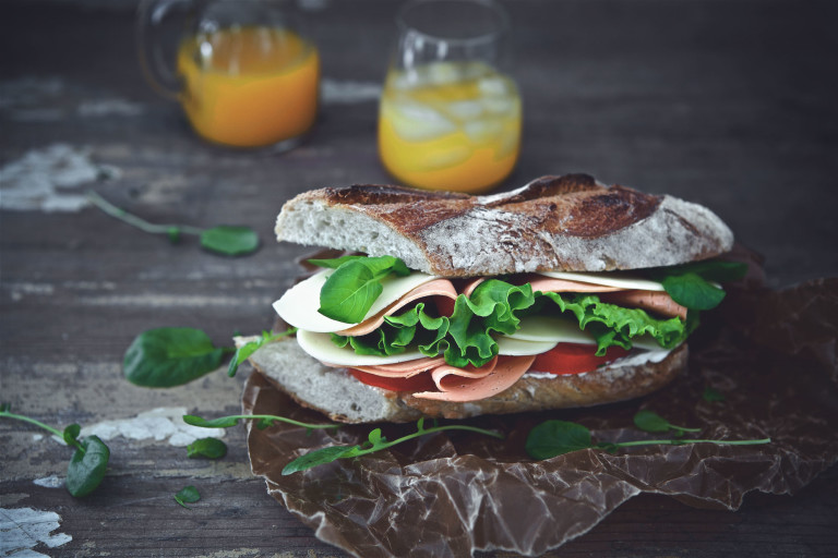 A sandwich on a rustic baguette filled with Quorn Vegan Ham Slices, tomato slices, lettuce, and cheese with a carafe and glass of orange juice in the background.