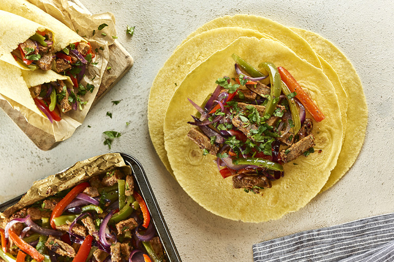 Open vegetarian fajita wraps with filling next to closed wraps and baking tray of filling