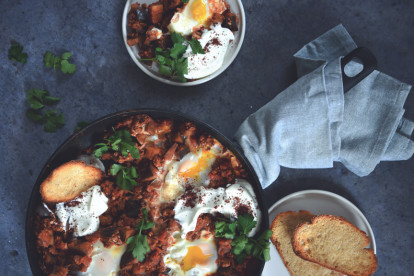 Shakshuka of Quorn Mince and aubergine and eggs, served in a dish next to a plate of toasts and a serving of shakshuka
