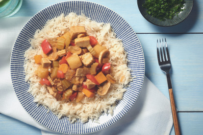 A curry made of Quorn Pieces, mushrooms, peppers, celery, and pineapple atop a bed of white rice.