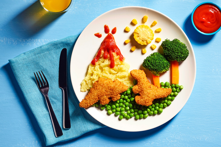 Two Quorn Roarsomes Vegan Dinosaur Nuggets against a backdrop of peas, carrot and broccoli trees, and a mashed potato volcano on a white plate.
