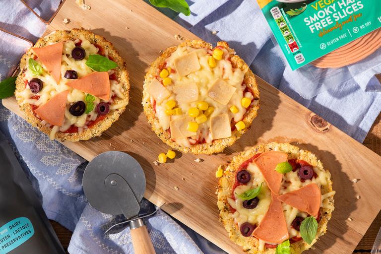 Mini cauliflower pizzas on wooden board positioned next to Quorn Vegan Ham Slices