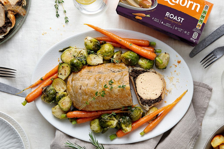 A vegetarian wellington made with Quorn Roast wrapped in mushrooms duxelles and puff pastry surrounded by roasted brussels sprouts and carrots with roast potatoes on the side.