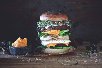 Vegetarian burger made with Quorn Ultimate Burgers layered with half a bun, lettuce, cheese, sweet potato mash and beansprouts