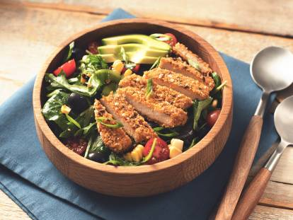A mixed green salad with corn, cherry tomatoes, and olives topped with sliced avocado and a sliced Quorn Vegan Meatless Chipotle Cutlet in a wooden bowl with wood-handled utensils to the right.