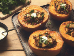 Four small pumpkins halved and baked stuffed with Quorn Pieces and quinoa, topped with yogurt and parsley on a baking sheet.