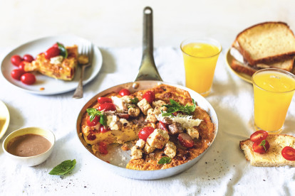 A frittata with Quorn Pieces, tomatoes, and basil served in a pan alongside toast, a balsamic cream dressing in a small bowl, and two glasses of orange juice.