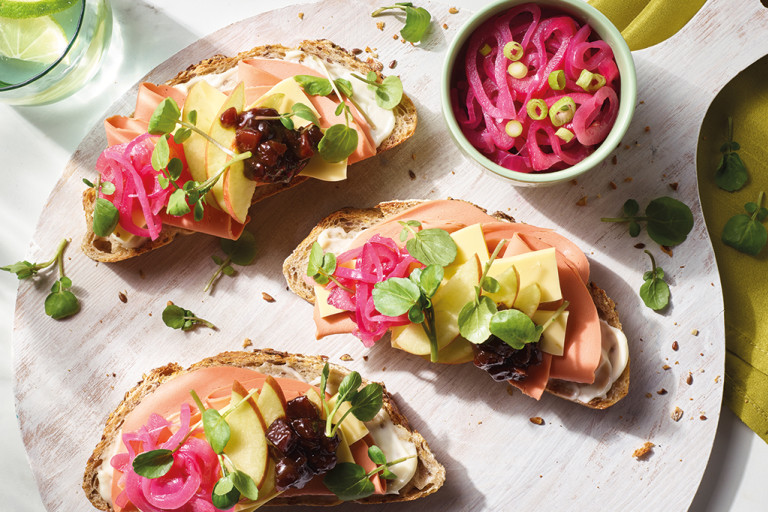 Three open-faced vegan ploughman's sandwiches topped with Quorn Vegan Smoky Ham Free Slices, Violife Epic Mature Cheddar Block slices, apple slices, ploughman's relish, pea shoots, and pickled onions arranged on a board.