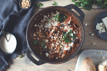 A stew made with Quorn Meatless Strips topped with tahini, pine nuts, and cilantro in a black Dutch oven.