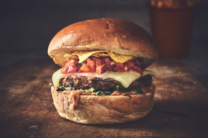 Veggie burger made with Quorn Brilliant Burgers topped with cheese, relish and nachos sandwiched between a bun