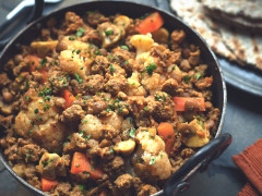 Meat free curry recipe made with Quorn Mince, cauliflower, carrots and lentils garnished with coriander served in a black pot