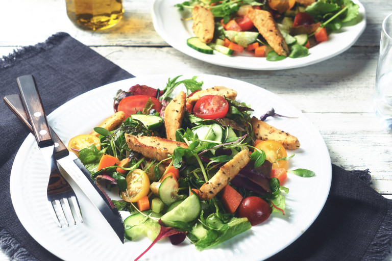 A romaine salad with cherry tomatoes, cucumber, carrots, and Quorn Strips served on a white plate.