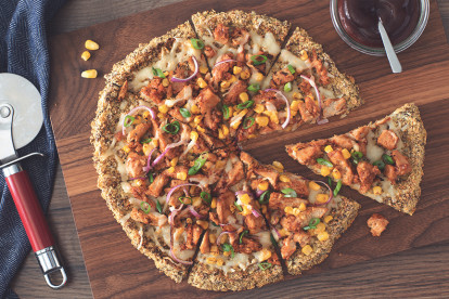 Quorn Strips, cheese, corn, red onion, and green onions atop a cauliflower crust on a wooden board with barbecue sauce and a pizza slicer on either side.