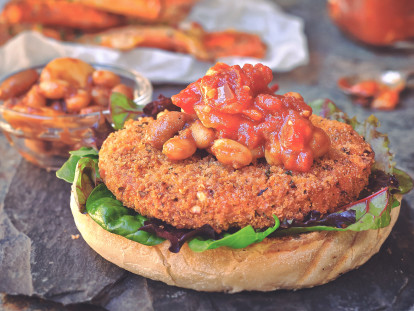 Healthy burger made with Quorn Vegan Hot and Spicy Burger served on a bed of salad in an open bun topped with bbq beans