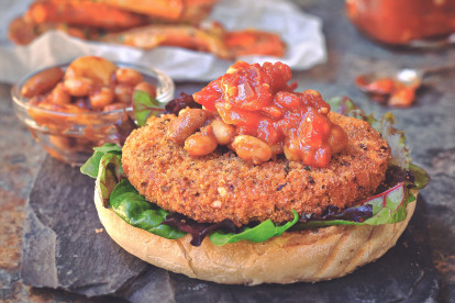 A Quorn Vegan Meatless Spicy Patty on the bottom of a burger bun topped with mixed greens, spicy beans, and a tomato relish on a slate tray with a small glass bowl of beans in the background.