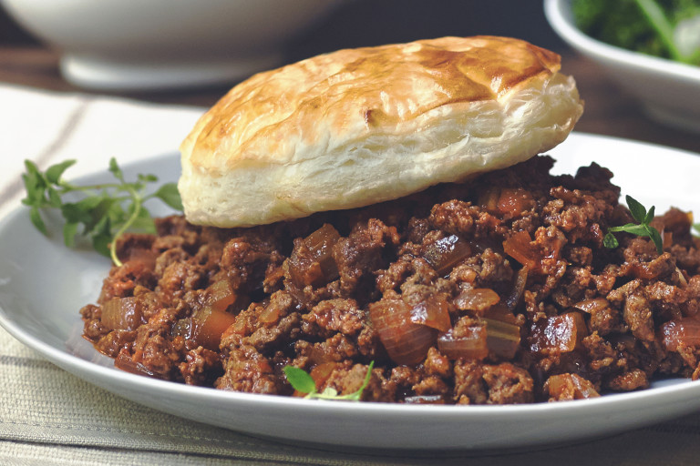 Vegetarian pie made with Quorn Mince and onions served on a plate topped with a pastry lid and sprigs of thyme