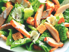 Pieces of romaine lettuce topped with Caesar dressing, parmesan, black pepper, croutons, and sliced Quorn Fillets.