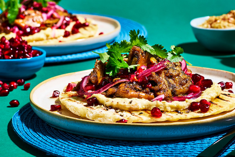 Flatbread topped with Quorn Makes Amazing Turkish Style Kebab, hummus, pickled red onion, pomegranate, coriander, and honey & lemon dressing on a blue placemat on a jade green backdrop.