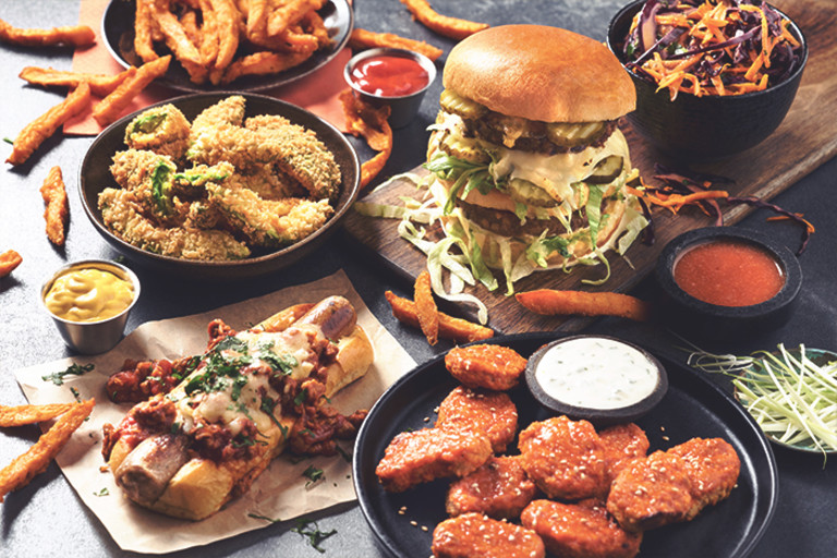 A burger, a chili cheese dog, nuggets in a sriracha glaze with blue cheese dressing on the side, a fried snack, carrot and red cabbage slaw, and sweet potato fries are arranged on a table with ramekins of sauces in between.