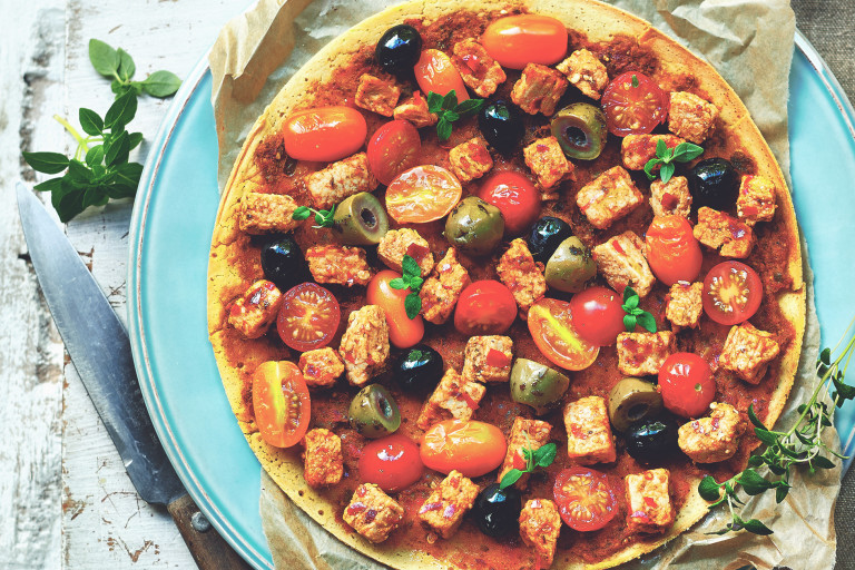 A socca pancake topped with black and green olives, grape tomatoes, microbasil, and Quorn Pieces on a piece of parchment atop a Tiffany blue plate with a knife to the left.